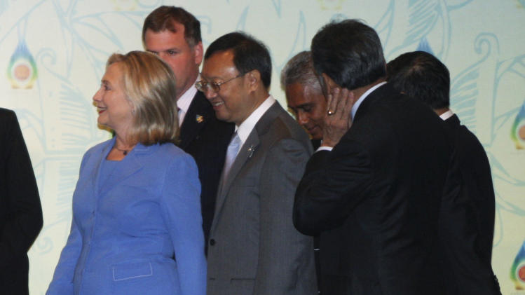 U.S. Secretary of State Hillary Rodham Clinton, in blue, walks with Chinese Foreign Minister Yang Jiechi, center, and other ministers after a group photo prior to the start of ASEAN Regional Forum Retreat Session in Nusa Dua, Bali, Indonesia, Saturday, July 23, 2011. Clinton is urging China and its Southeast Asian neighbors to show restraint in disputed waters in the South China Sea. (AP Photo/Dita Alangkara)