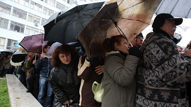 """People line up for free meat lunches under a rainfall in Athens on Thursday, March 7, 2013. It's called """"Barbecue Thursday"""" _ a raucous pre-Easter celebration for meat lovers. But this year's Tsiknopempti festivities, a fixture of the Carnival season, coincided with the Greek Statistical Authority announced unemployment in Greece has dipped marginally to 26.4 percent, according to data for December. (AP Photo/Thanassis Stavrakis)"""
