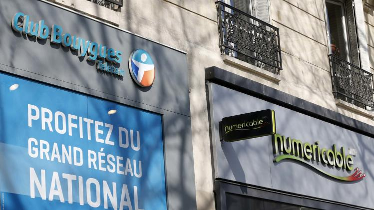 The storefronts of a Bouygues phone shop and cable operator Numericable are seen in Paris