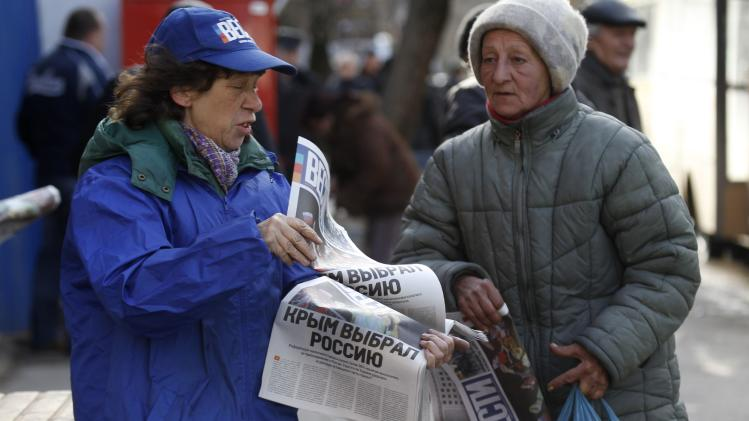 "A woman hands out free newspapers with the headline ""Crimea chooses Russia"" on a street in Simferopol"