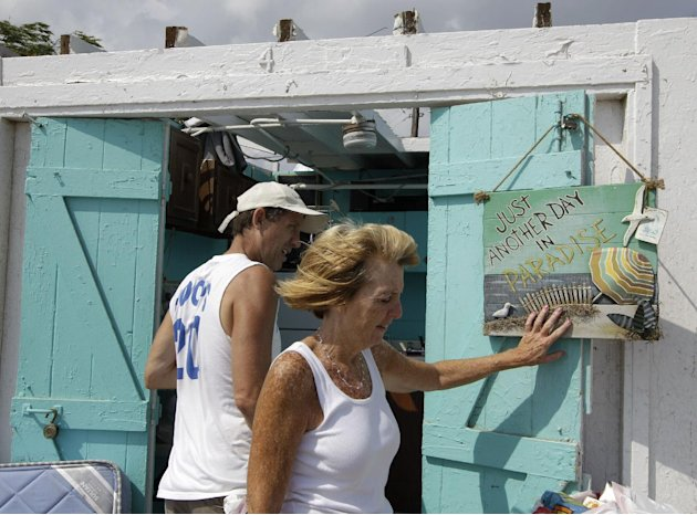 Bill Ryan watches as his wife Janet hangs up a picture in front of their roofless cabana at the Breezy Point Surf Club in the Queens section of New York, Saturday, Sept. 8, 2012, after severe weather