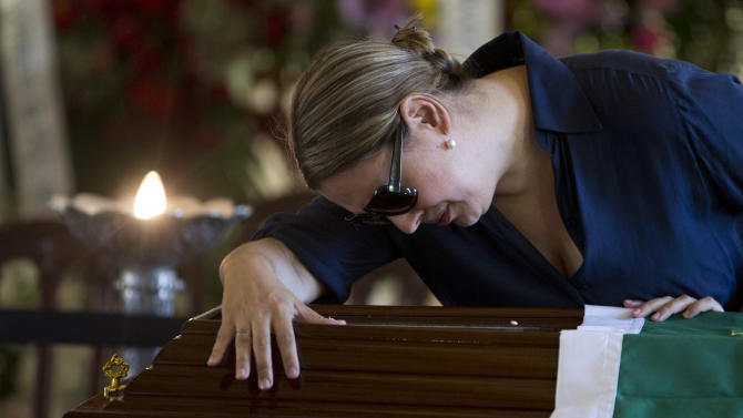 "A woman reacts by the coffin containing the remains of Brazilian architect Oscar Niemeyer, at the ""Palacio da Cidade"" or ""City Palace"", in Rio de Janeiro, Friday, Dec. 7, 2012. Niemeyer, 104, the groundbreaking architect who designed Brazil's futuristic capital and much of the United Nations complex, died Wednesday night in Rio de Janeiro, the seaside city where he was born and where his remains will be buried. (AP Photo/Felipe Dana)"