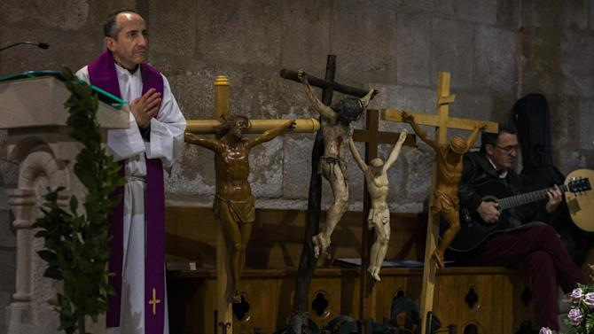 """A member of a church prays during a Mass as penitents from """"Las Siete Palabras (Seven words)"""" brotherhood get ready to take part in a procession in Zamora, Spain, on the early hours of Wednesday, April 1, 2015. Hundreds of processions take place throughout Spain during the Easter Holy Week. (AP Photo/Andres Kudacki)"""