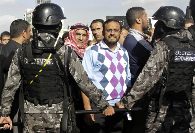Jordanian police stand guard during a protest against the government's decision to raise prices for subsidized fuel in Amman, Jordan, Monday, Nov. 19, 2012. Nearly a week after the announcement, which sparked unrest that left one person dead and scores wounded, protests across the country continued. The protests have included rare demands for King Abdullah II to be deposed. (AP Photo/Raad Adayleh)