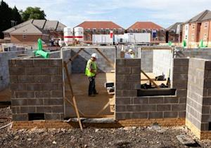 Workers construct residential homes at a building site in north London