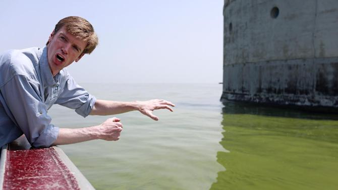 Collin O'Mara, president and CEO of the National Wildlife Federation, gestures as he talks about algae near the City of Toledo water intake crib, Sunday, Aug. 3, 2014, in Lake Erie, about 2.5 miles off the shore of Curtice, Ohio. More tests are needed to ensure that toxins are out of Toledo's water supply, the mayor said Sunday, instructing the 400,000 people in the region to avoid drinking tap water for a second day. Toledo officials issued the warning early Saturday after tests at one treatment plant showed two sample readings for microcystin above the standard for consumption, possibly because of algae on Lake Erie. (AP Photo/Haraz N. Ghanbari)