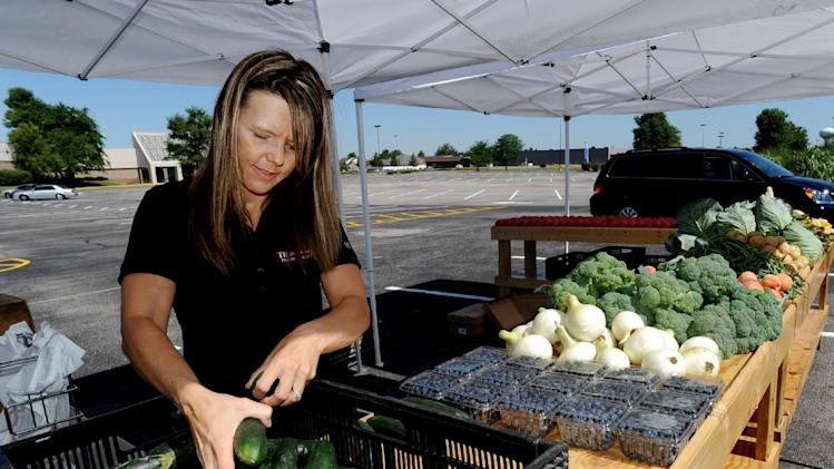 FILE - In this June 13, 2012 file photo, Julie Trunnell, with Trunnell's Farm Market, unloads cucumbers along with other locally grown produce in the parking lot at Towne Square Mall, in Owensboro, Ky. U.S. wholesale prices rose only slightly last month, as higher costs for food and pickup trucks offset another drop in energy prices, according to the Labor Department, Friday, July 13, 2012. But overall inflation stayed mild. (AP Photo/The Messenger-Inquirer, Gary Emord-Netzley, File)