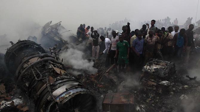 FILE- In this June. 3, 2012 file photo, people gathered at the site of a plane crash in Lagos, Nigeria,  Seven months after one of Dana Air planes crashed, killing at least 163 people, the Nigerian airline has resumed domestic flights in the West African nation. Dana Air sold tickets Thursday Jan. 3, 2013 for flights between Nigeria's capital, Abuja, and its largest city of Lagos. It was an Abuja-Lagos flight that crashed on June 3 in a densely populated neighborhood near Murtala Muhammed International Airport in Lagos, killing 153 people on board and at least 10 on the ground. (AP Photo/Sunday Alamba File)