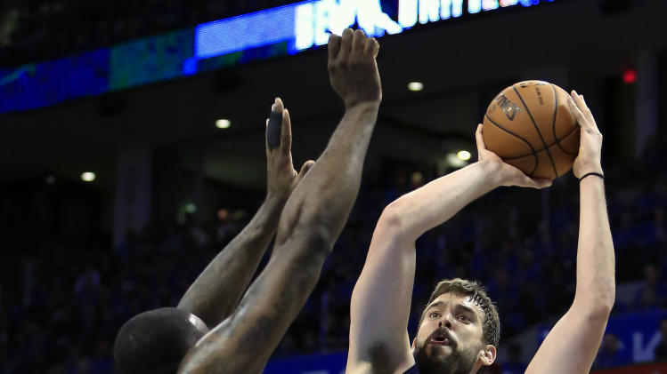 Memphis Grizzlies center Marc Gasol (33) shoots as Oklahoma City Thunder center Kendrick Perkins (5) defends during the second quarter of Game 1 of the opening-round NBA basketball playoff series in Oklahoma City on Saturday, April 19, 2014. (AP Photo/Alonzo Adams)