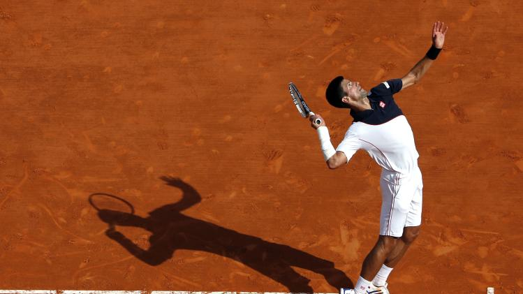 Djokovic serves to Federer during their semi-final match at the Monte Carlo Masters in Monaco