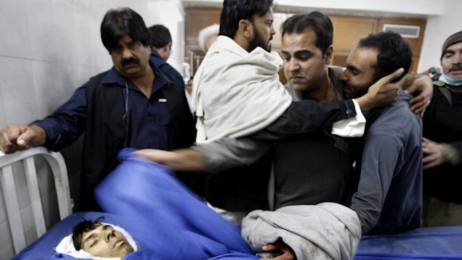People comfort to a person, right, mourning over the death of his relative, a victim of a rocket attack by militants, at a local hospital in Peshawar, Pakistan on Saturday, Dec. 15, 2012. Militants fired three rockets at an airport in the northwestern Pakistani city of Peshawar on Saturday night, killing several people and wounding dozens, officials said. (AP Photo / Mohammad Sajjad)