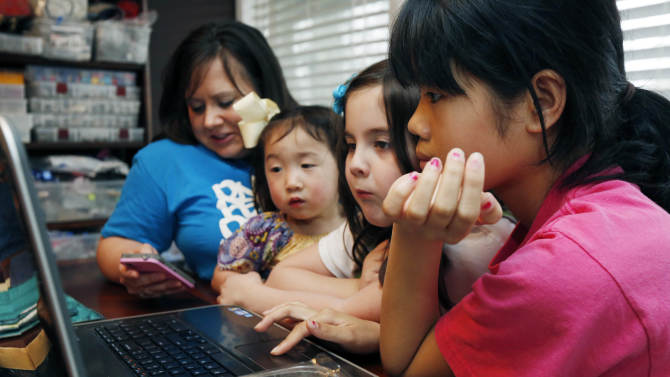 """In this April 4, 2013 photograph, the Smith women, from left, mother Niki Smith, GiGi, 3, Macy Jade, 7 and Guan Ya, 14, use Google Translate on the family laptop to """"speak"""" with their new daughter, Guan Ya, in their Rienzi, Miss., home. The Smiths and their children are using the Google Translate program to communicate almost exclusively with Guan Ya, who is deaf. The family uses iPhones, iPods and a laptop, all loaded with the program to write in either English that translates to Chinese or vice-a-versa. (AP Photo/Rogelio V. Solis)"""