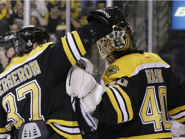 Boston Bruins center Patrice Bergeron (37) congratulates Boston Bruins goalie Tuukka Rask (40), of Finland, on his shutout to beat the Chicago Blackhawks 2-0 in Game 3 of the NHL hockey Stanley Cup Fi