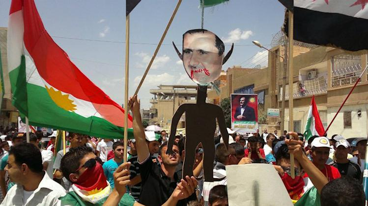 "FILE - This Friday, June 15, 2012 file citizen journalism image provided by Shaam News Network SNN purports to show anti-Syrian regime Kurdish protesters holding an effigy of Syrian President Bashar Assad as they wave their Kurdish flag during a demonstration called the ""Friday of Russia is the enemy of Syrian people,"" at the northeastern town of Amouda, Syria. (AP Photo/Shaam News Network, SNN, File )THE ASSOCIATED PRESS IS UNABLE TO INDEPENDENTLY VERIFY THE AUTHENTICITY, CONTENT, LOCATION OR DATE OF THIS HANDOUT PHOTO"