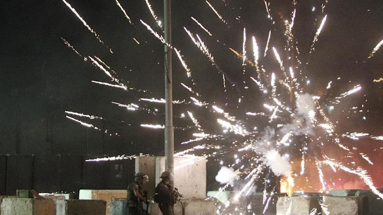 Israeli border guards take position as fireworks launched by Palestinian protestors light the sky during clashes at the Qalandia checkpoint between Jerusalem and Ramallah, early on July 12, 2014