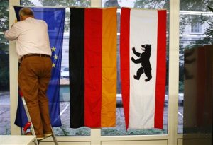 An election volunteer adjusts flags of the EU, Germany…