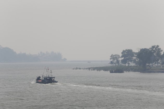 Fishermen boats leave for the haze-covered Strait of Malacca from the mouth of Muar River in Muar