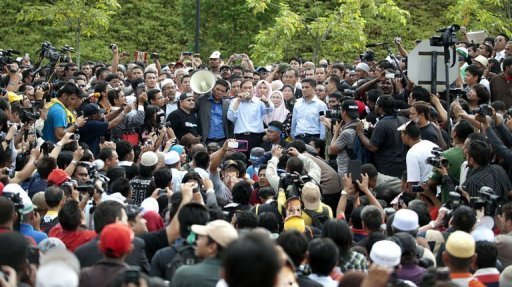 Anwar Ibrahim (C) speaks to his supporters outside the court after his verdict