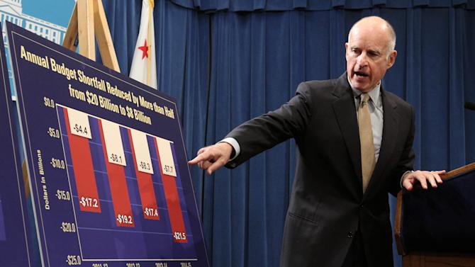 Gov. Jerry Brown points to a chart showing how his budget plans will eventually reduce the budget deficit over the next few years  as he discusses his revised state budget plan during a Capitol news conference in Sacramento, Calif., Monday,  May 14, 2012.  Brown said the budget shortfall swelled from $9.2 billion predicted in January to $16 billion, in part because tax collections have not come in as high as expected and  lawsuits and federal requirements that have blocked billions of dollars in state cuts. (AP Photo/Rich Pedroncelli)