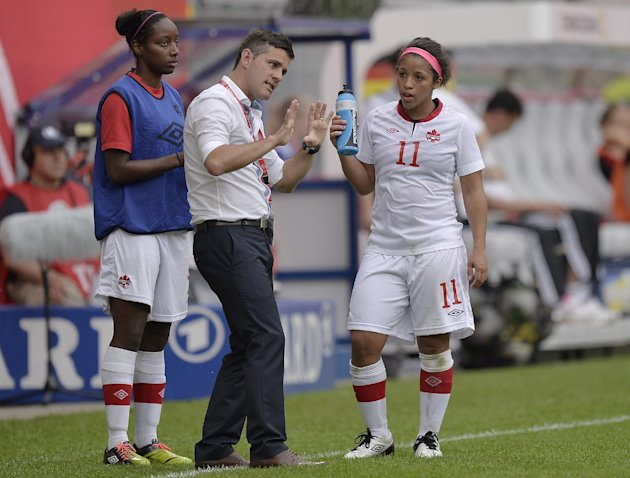 Canada's head coach John Herdman talks to Desiree Scott, right, during the international women's friendly soccer match between Germany and Canada in Paderborn, Germany, Wednesday, June 19,  2013
