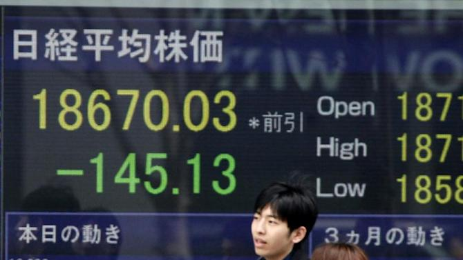 Passersby wait to cross a street in front of Japan's Nikkei stock index displayed on an electronic board in Tokyo, Wednesday, March 4, 2015. Asian stock markets were mostly lower Wednesday after Wall Street declined and investors looked ahead to U.S. economic data and China's announcement of its annual growth target. (AP Photo/Shuji Kajiyama)