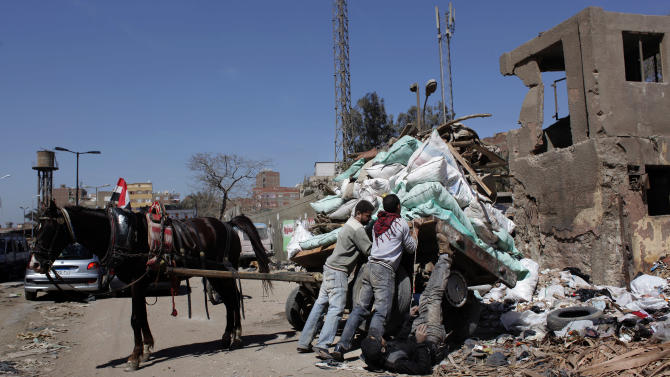 In this Friday, March 9, 2012 photo, Egyptian men dispose garbage and construction material loaded on a cart onto the sidewalk of a road in Cairo, Egypt. The streets and sidewalks of Cairo have always been rather chaotic. But they've only gotten worse in the political turmoil as Egypt stumbles towards a new system following the fall of President Hosni Mubarak. (AP Photo/Nasser Nasser)