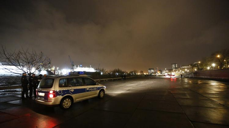 Police officers monitor a parking lot near the famous landmark fish market in the harbour of Hamburg