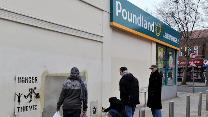 "People look at  section of wall   Saturday Feb.23, 2013 where a Banksy mural was removed from the side of a Poundland shop north London in mysterious circumstances, only to reappear on the website of a Miami auction house. Listed as ""Slave Labor (Bunting Boy),"" it was due to be sold Saturday with an estimated price of between $500,000 and $700,000. Slave Labour, which shows a young boy hunched over a sewing machine making Union Jack bunting, appeared on the wall  last May, just before the Diamond Jubilee celebrations. (AP Photo/John Stillwell/PA) UNITED KINGDOM OUT - NO SALES - NO ARCHIVES"