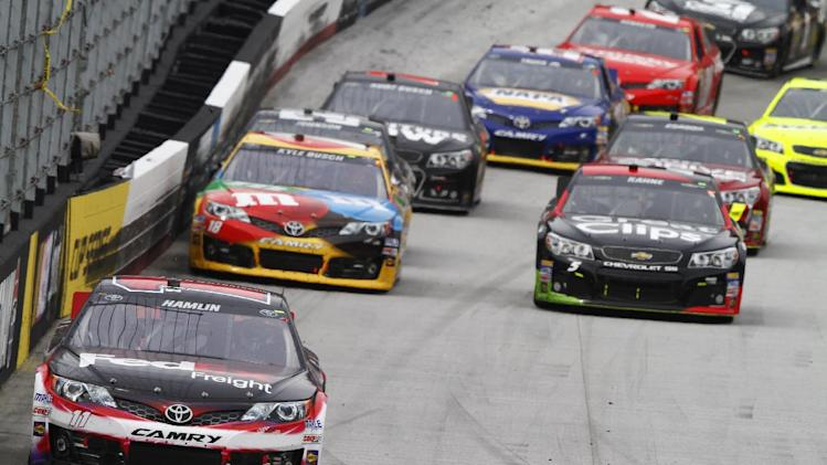 Denny Hamlin (11) leads driver Kyle Busch (18), driver Kasey Kahne (5) and others during the NASCAR Sprint Cup Series Food City 500 auto race on Sunday, March 17, 2013, in Bristol, Tenn. (AP Photo/Wade Payne)