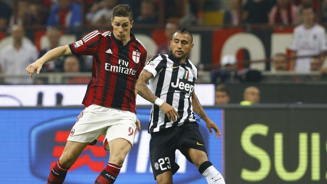 AC Milan's Torres challenges Juventus' Vidal during their Italian Serie A soccer match at the San Siro stadium in Milan