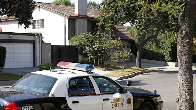 """An unoccupied Los Angeles County Sheriff's Department patrol car is parked across from the home, background, of Nakoula Basseley Nakoula, the man who made the film """"Innocence of Muslims"""" that has sparked violent protests, in Cerritos, Calif., Tuesday, Sept. 25, 2012. The filmmaker has received death threats and was forced into hiding, putting his home up for sale, after the 14-minute movie trailer rose to prominence. (AP Photo/Reed Saxon)"""