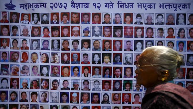 A woman walks past the portraits of people who died during the April earthquake in Bhaktapur