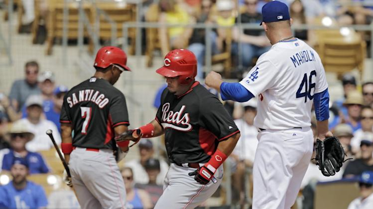 onCincinnati Reds' Brayan Pena, center, comes home to score on a wild pitch by Los Angeles Dodgers starting pitcher Paul Maholm (46) in the second inning of a spring exhibition baseball game on Thursday, March 13, 2014, in Glendale, Ariz