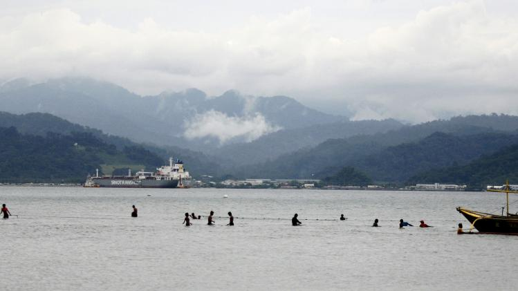 Residents hold onto their nets as they fish in the shallow waters near Subic Bay Freeport in Subic