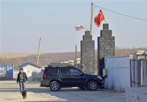 """A man walks past the gates of the """"Armada"""" farming project run by Dongning Huaxin Group near the far eastern Russian town of Ussuriysk"""