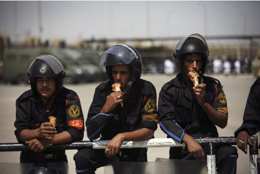 Egyptian riot police eat ice cream while securing the courthouse where ex-President Hosni Mubarak received a verdict in his trial for charges related to the death of protesters in Cairo, Egypt, Saturday, May 2, 2012. Egypt's ex-President Hosni Mubarak was sentenced to life in prison Saturday for his role in the killing of protesters during last year's revolution that forced him from power, a verdict that caps a stunning fall from grace for a man who ruled the country as his personal fiefdom for nearly three decades. (AP Photo/Manu Brabo)