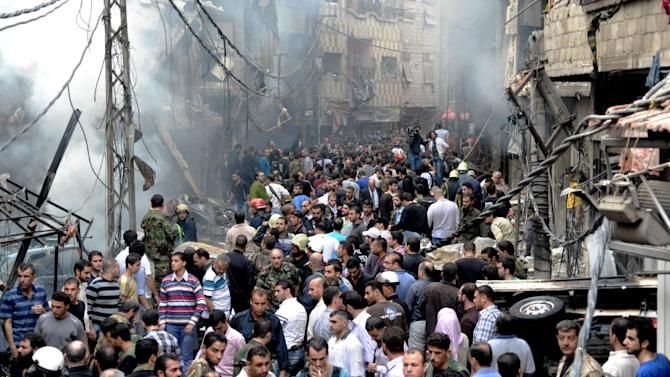 This photo released by the Syrian official news agency SANA, shows Syrians standing at the scene after a blast occurred according to footage and reports shown on State-run Al-Ikhbariya television in the Mazzeh al-Jabal district of the Syrian capital Damascus, Syria, Monday, Nov. 5, 2012. Several people were killed and injured, among them children, Al-Ikhbaria said. (AP Photo/SANA)