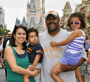 """This June 2013 photo provided by Disney PhotoPass Service shows Creed Anthony of Indianapolis with his daughter Sophie, 5, son Isaac, 2, and wife Amal, on a visit to Disney World's Magic Kingdom in Lake Buena Vista, Fla. Anthony is an example of a new generation of hands-on dads who don't just change the occasional diaper but who view """"parenting as a partnership,"""" as he put it,  by being as involved in childrearing as moms. (AP Photo/Disney PhotoPass Service)"""