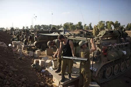 Israeli soldiers prepare APCs outside the Gaza Strip