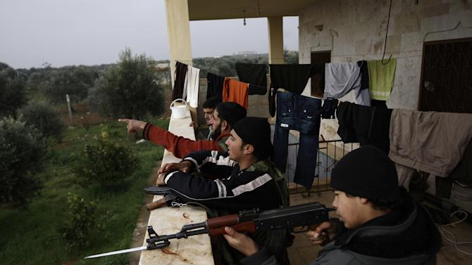 In this Monday, Dec. 17, 2012 photo, Syrian rebels prepare themselves before attending a training session in Maaret Ikhwan, near Idlib, Syria. The training is part of an attempt to transform the rag-tag rebel groups into a disciplined fighting force. (AP Photo/Muhammed Muheisen)