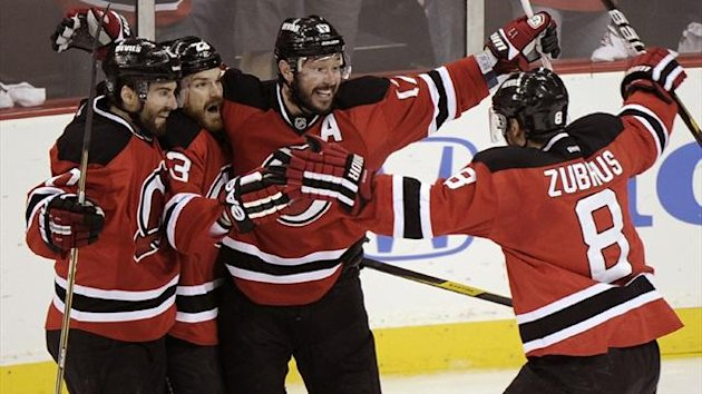 2011-12 NHL New Jersey Devils' Ilya Kovalchuk (C) celebrates with teammates Dainius Zubrus (R), David Clarkson (2nd from L) and Peter Harrold (L)