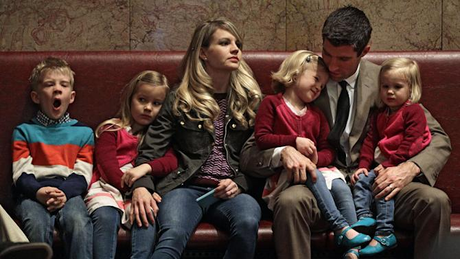 Colorado Senator Owen Hill, second from right, sits with his wife Emily and their children, who came to visit him inside the senate chamber at the State Capitol, in Denver, Friday March 8, 2013.  Colorado Senate Democrats advanced an expansion of background checks on firearm purchases as part of a package of bills responding to the shootings in Aurora and Connecticut.  The proposal would require background checks where they currently don't exist, such as purchases online and private sales and transfers. The bill got initial approval in the Senate on an unrecorded vote on Friday.  (AP Photo/Brennan Linsley)