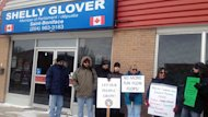 Protesters gather outside Conservative MP Shelly Glover's office in Winnipeg on Thursday.