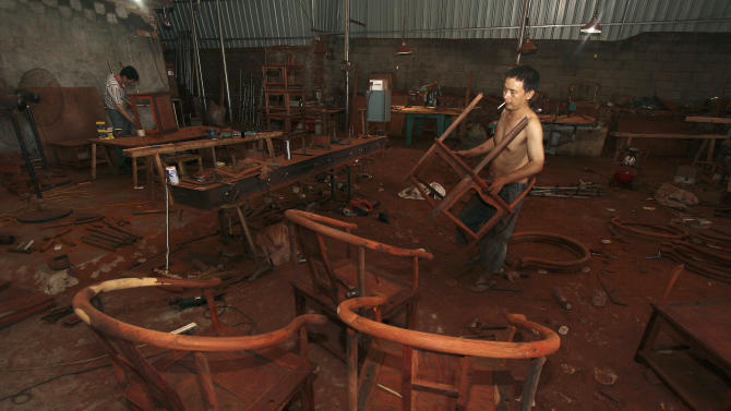 In this photo taken on Aug. 11, 2012, laborers work at a furniture factory in Xianyou county in southeast China's Fujian province. China's premier said Wednesday, Aug. 15, 2012 the country should meet this year's economic targets but is warning hardship could continue for some time and trade conditions will be grim. (AP Photo) CHINA OUT