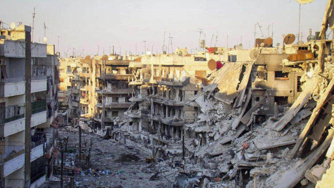 In this picture taken on Wednesday Oct. 31, 2012, a citizen journalism image provided by Lens Young Homsi, which has been authenticated based on its contents and other AP reporting, buildings which were destroyed from the shelling by Syrian forces loyal to Syrian president Bashar Assad, at al-Qossour neighborhood in Homs province, central Syria. Syrian warplanes fired missiles at opposition strongholds around Damascus and in the north on Wednesday as Turkey, a key backer of the anti-regime rebels, appeared to distance itself from an earlier call to impose a no-fly zone. (AP Photo/Lens Yong Homsi)