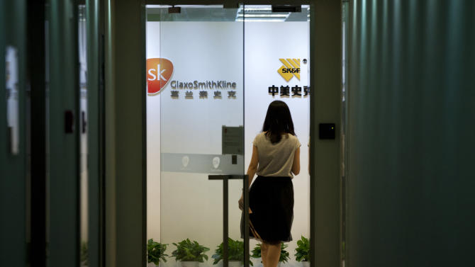 FILE - In this July 11, 2013 file photo, a woman enters an office of GlaxoSimthKline in Beijing, China. Chinese police have identified four managers of drug manufacturer GlaxoSmithKline who they accuse of paying millions of dollars in bribes to doctors and others, a state news agency reported Monday, July 15, 2013. The police ministry announced last week GSK employees were under investigation for paying bribes that were passed through travel agencies. It said the bribes were aimed at increasing sales.(AP Photo/Alexander F. Yuan, File)