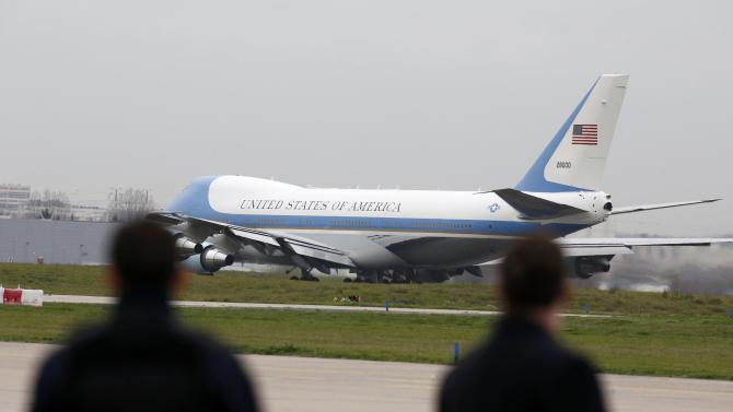 Security forces look at Air Force One as US President Barack Obama flies from Orly airport near Paris