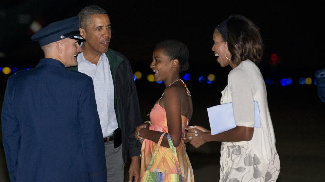 President Barack Obama, second from left, Sasha Obama, and first lady Michelle Obama, are greeted as they exit Air Force One on arrival at Andrews Air Force Base, Md., on Sunday Aug. 18, 2013, after a family vacation on the island of Martha's Vineyard. Also with them was Malia Obama, not pictured. (AP Photo/Jacquelyn Martin)