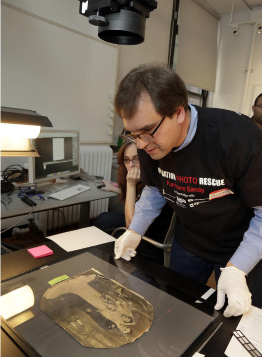 In this Saturday, Feb. 2, 2013 photo, Scott Geffert, senior imaging systems manager of New York's Metropolitan Museum of Art, prepares a damaged photo belonging to Florence Catania, of Deer Park, N.Y.