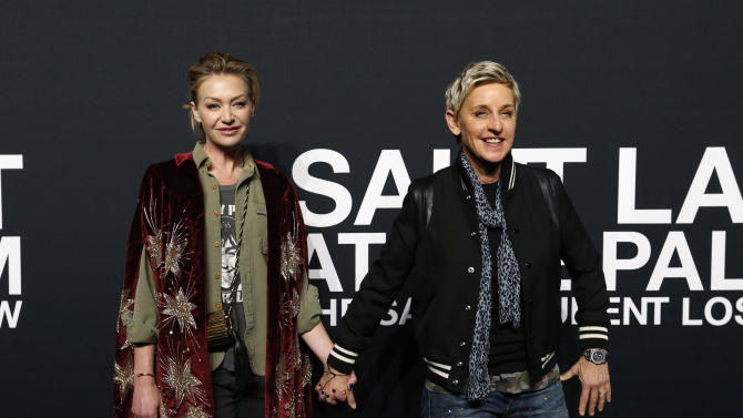 Television host DeGeneres and her wife actress de Rossi pose as they arrives for the Saint Laurent fall collection fashion show at the Hollywood Palladium in Los Angeles